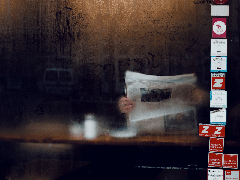 man_reading_a_newspaper_in_a_cafe